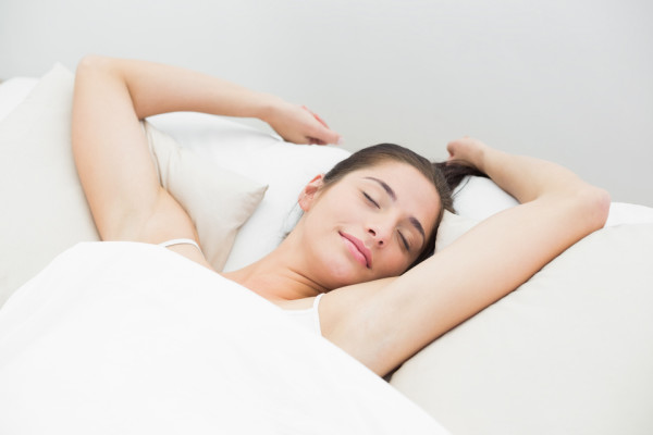 High angle view of a beautiful young woman sleeping in bed with eyes closed